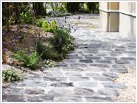 アンティーク石のアプローチと石張りテラスの庭